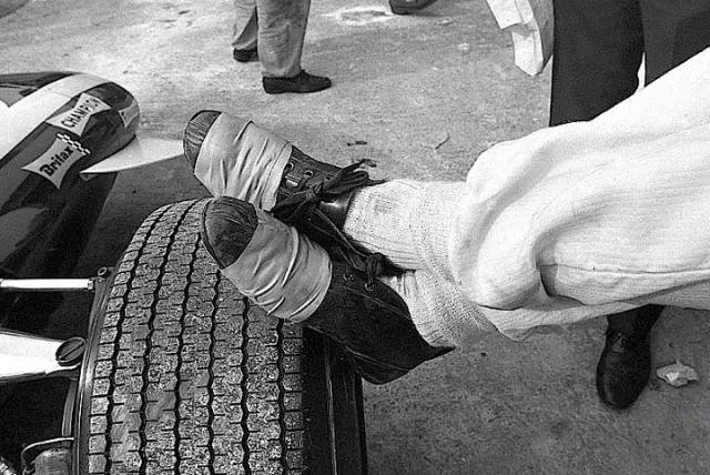 Le scarpe del pilota svizzero Jo Siffert appoggiate alla ruota della sua Lotus 49B all'Autodromo di Monza, nel 1968